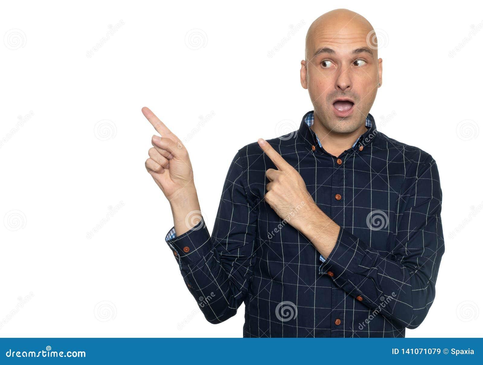 Szokujący łysy mężczyzna wskazuje palce na boku odosobniony