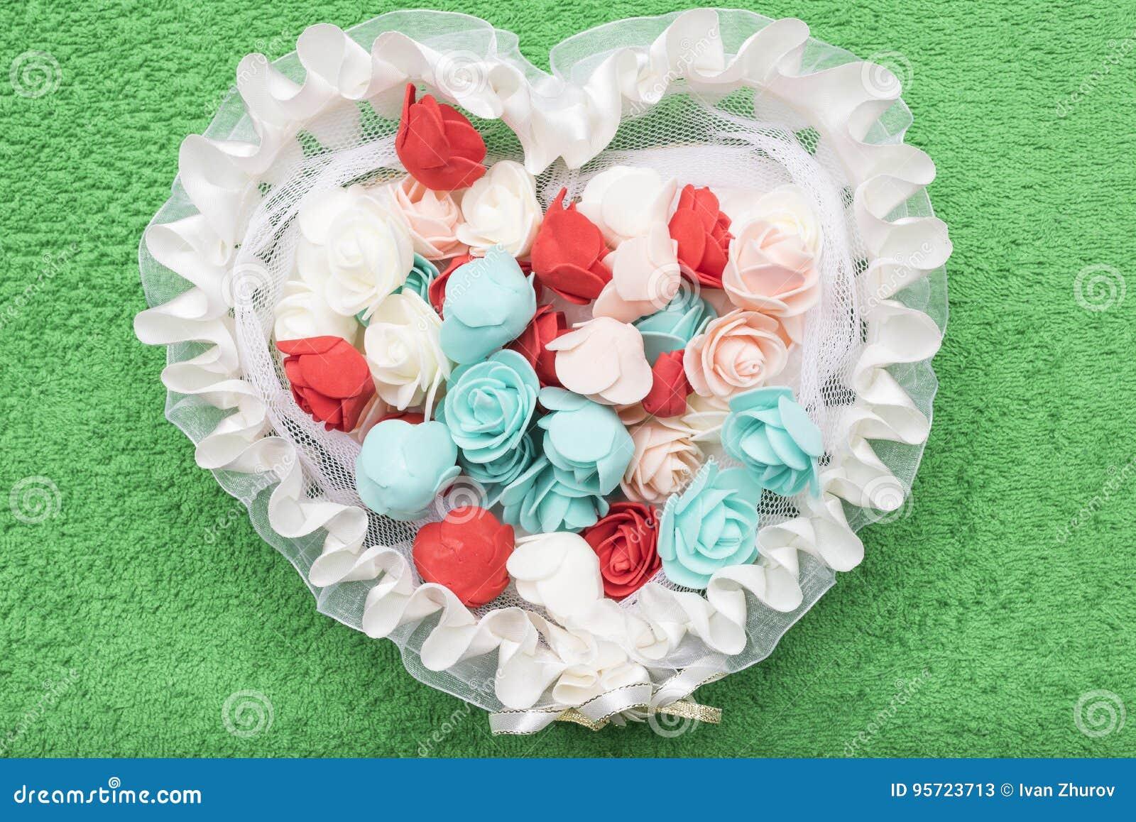 Sztuczne stubarwne róże kłamają w białym koronkowym koszu w postaci serca