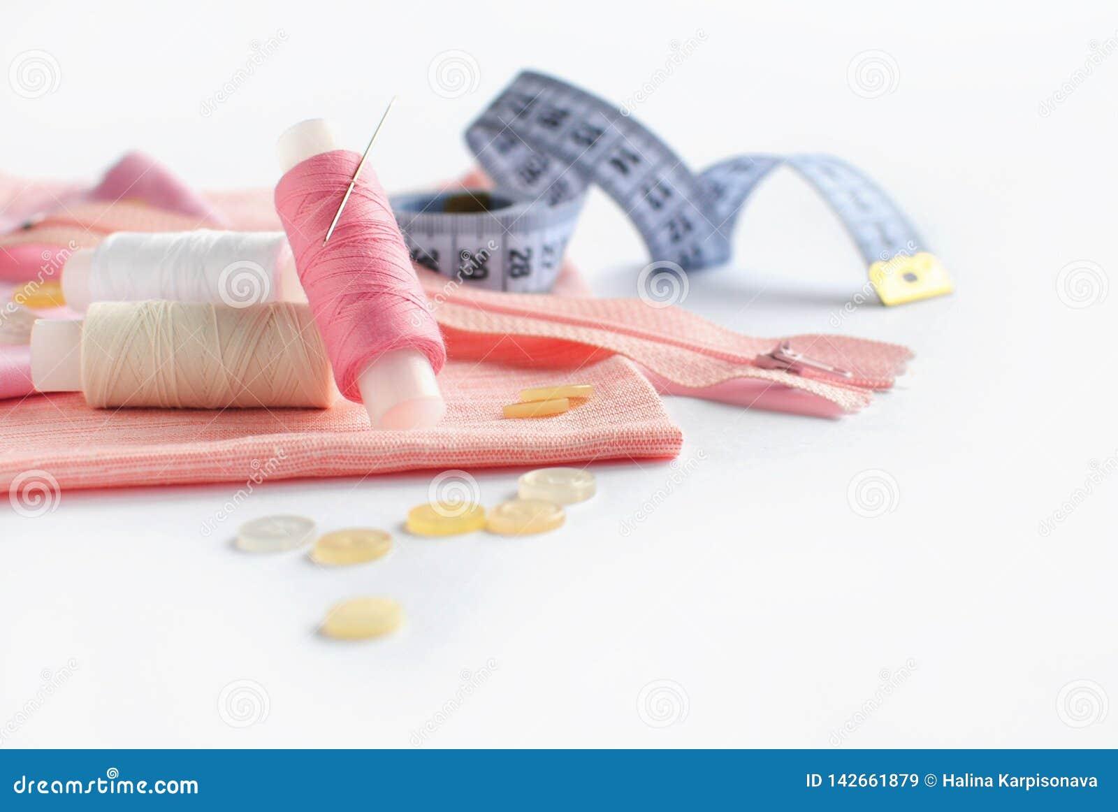 Szwalni akcesoria i różowa tkanina na białym tle Tkanina, szwalne nici, igła, suwaczek, guziki i szwalny centymetr,