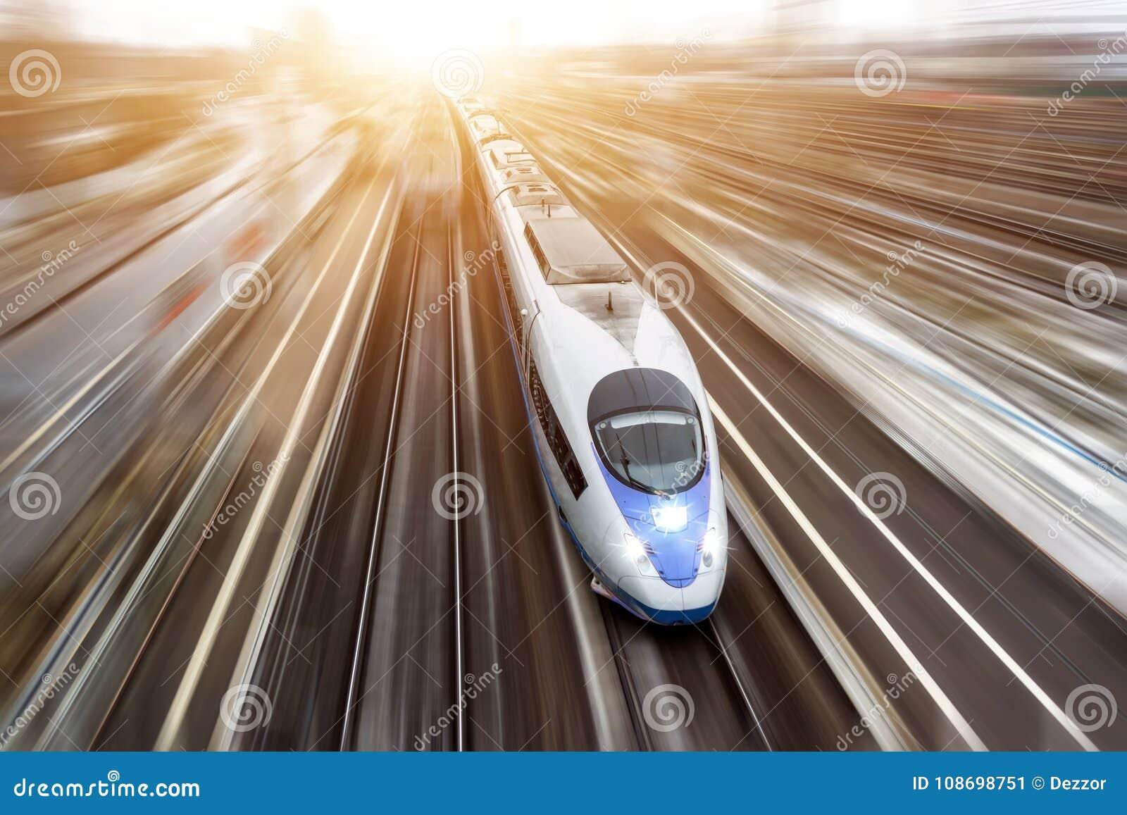 Szybkościowy pociąg pasażerski podróżuje przy wysoką prędkością Odgórny widok z ruchu skutkiem, smarujący tło