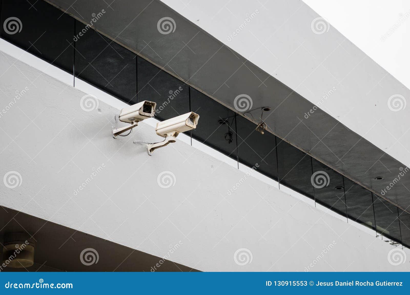 Tätt upp till två säkerhetskameror på strukturen av en byggnad med en stor spegel ovanför dem