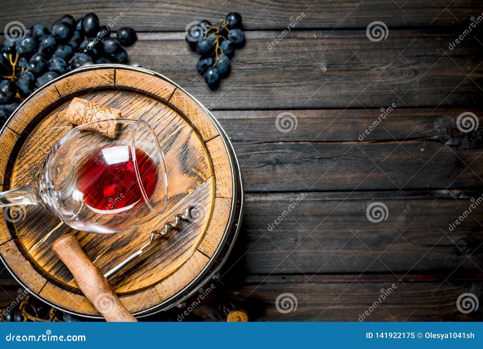 Tła szkła czerwone wino Baryłka z czerwonym winem i winogronami