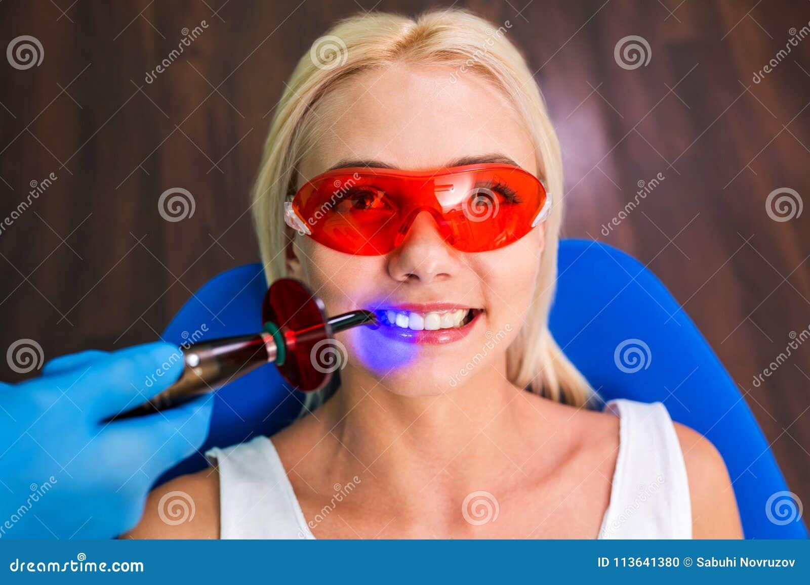 Tålmodigt sammanträde för kvinna på mottagandet med tandläkaren och händer med hjälpmedel