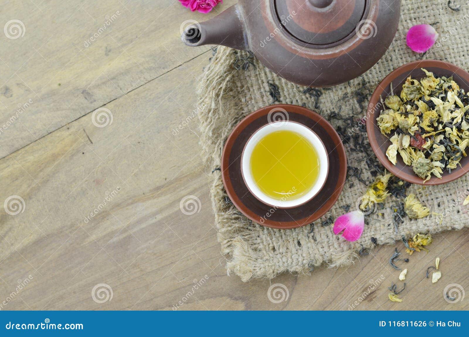 Tè asciutto e tè in tazza su fondo di legno