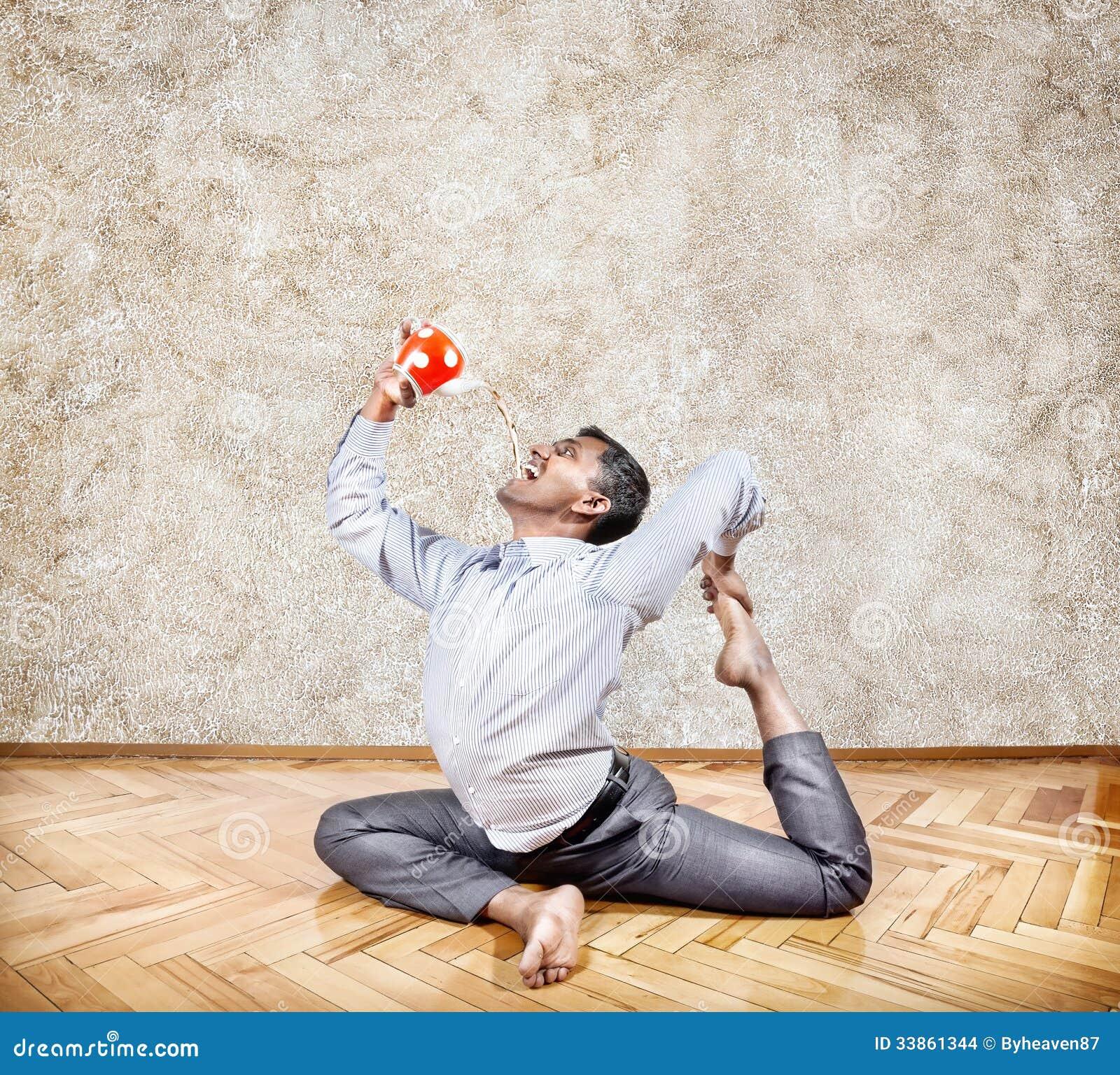 Tè bevente dell uomo d affari nella posa di yoga