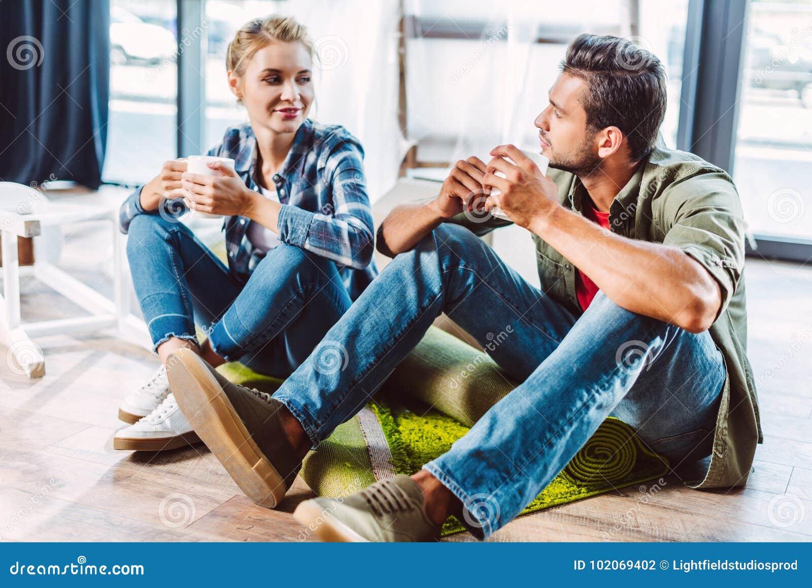 Tè bevente delle coppie in nuovo appartamento
