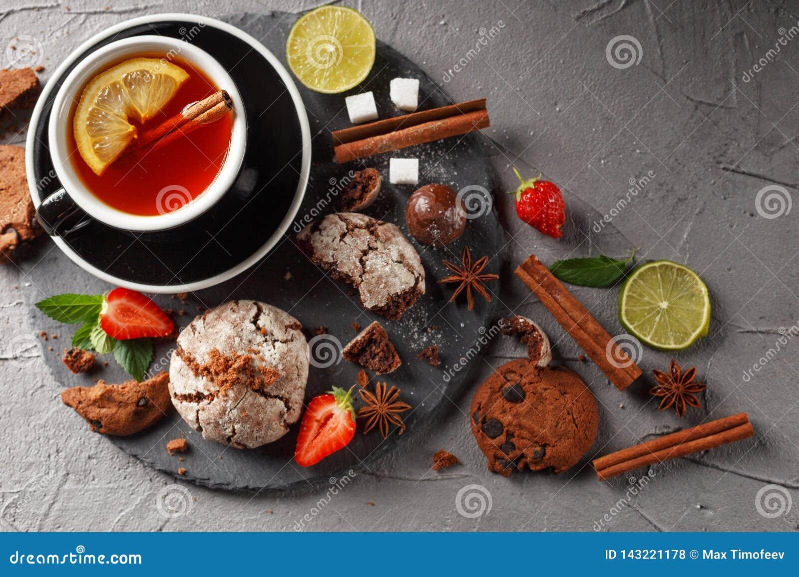 Tè fragrante in una tazza nera su una banda nera con i biscotti, il limone, la cannella ed i frutti