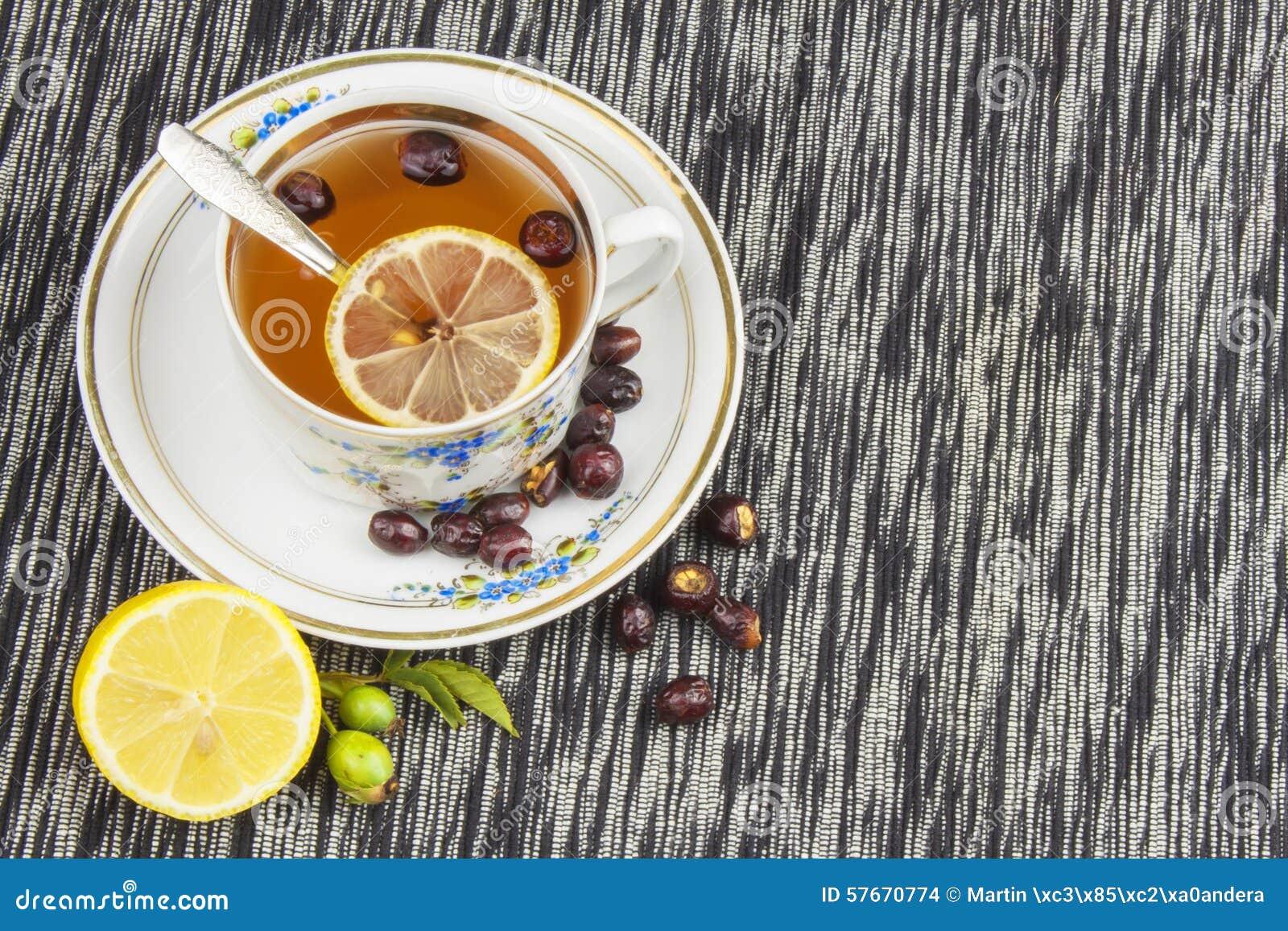 Té caliente con el limón y flecha roja en la tabla Tratamiento casero para los fríos y la gripe