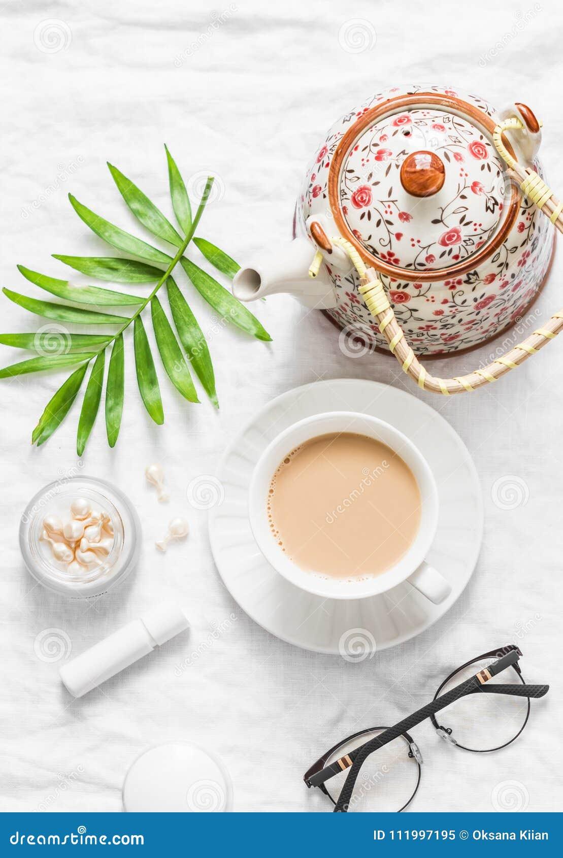 Té con leche Té de Masala, tetera, cosméticos, lápiz labial, aceite facial, vidrios, flor verde de la hoja en el fondo ligero, vi