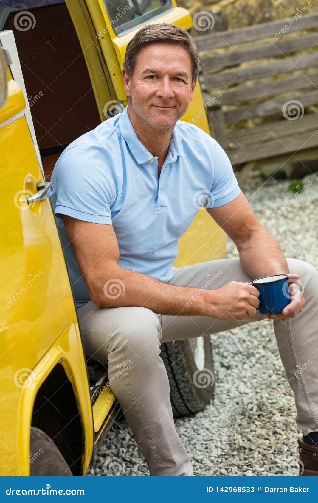 Té o café de consumición envejecido centro feliz del hombre que se sienta en Van