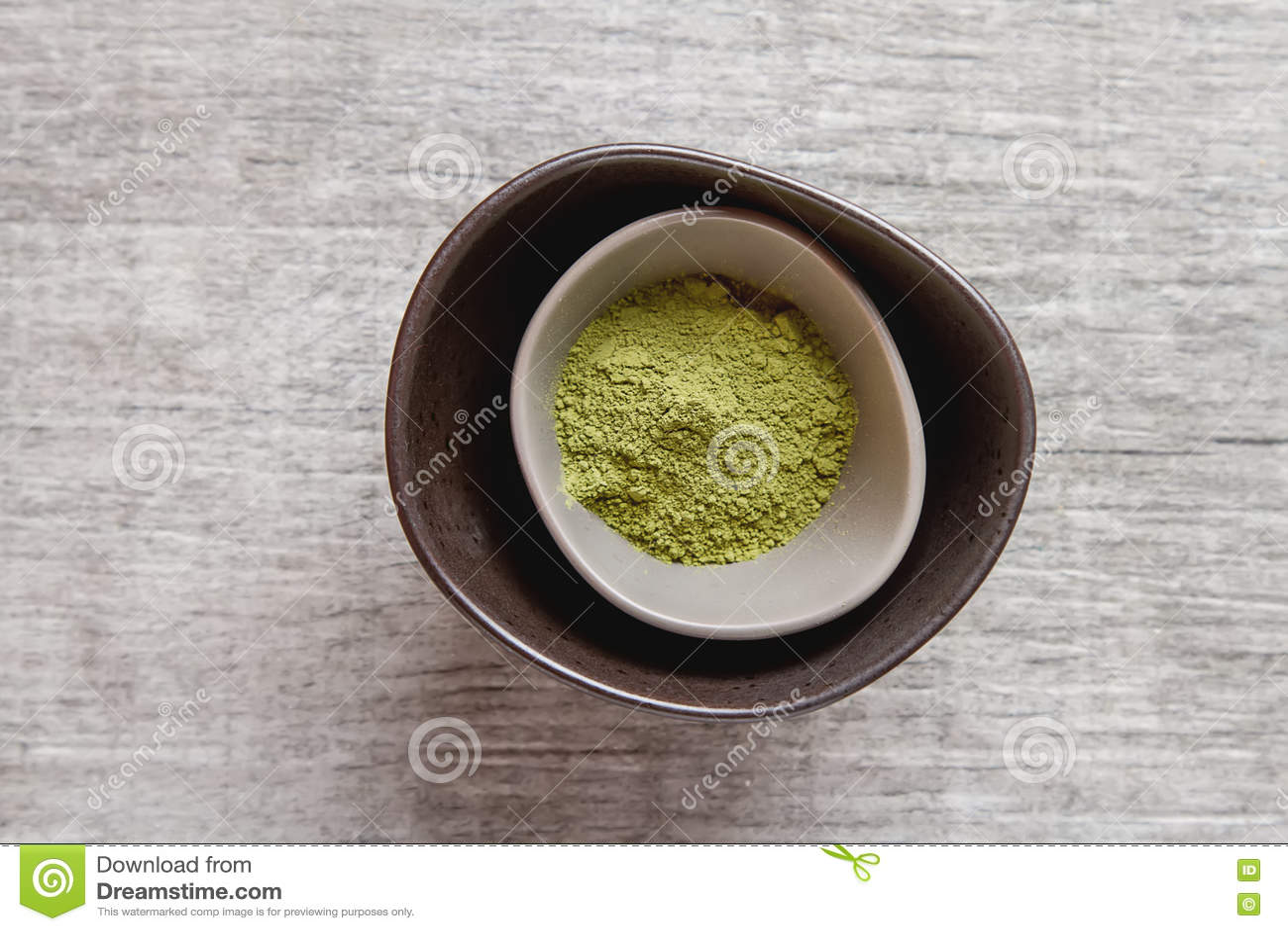 Té seco de Matcha en una pequeña placa marrón Fondo de madera gris tapa