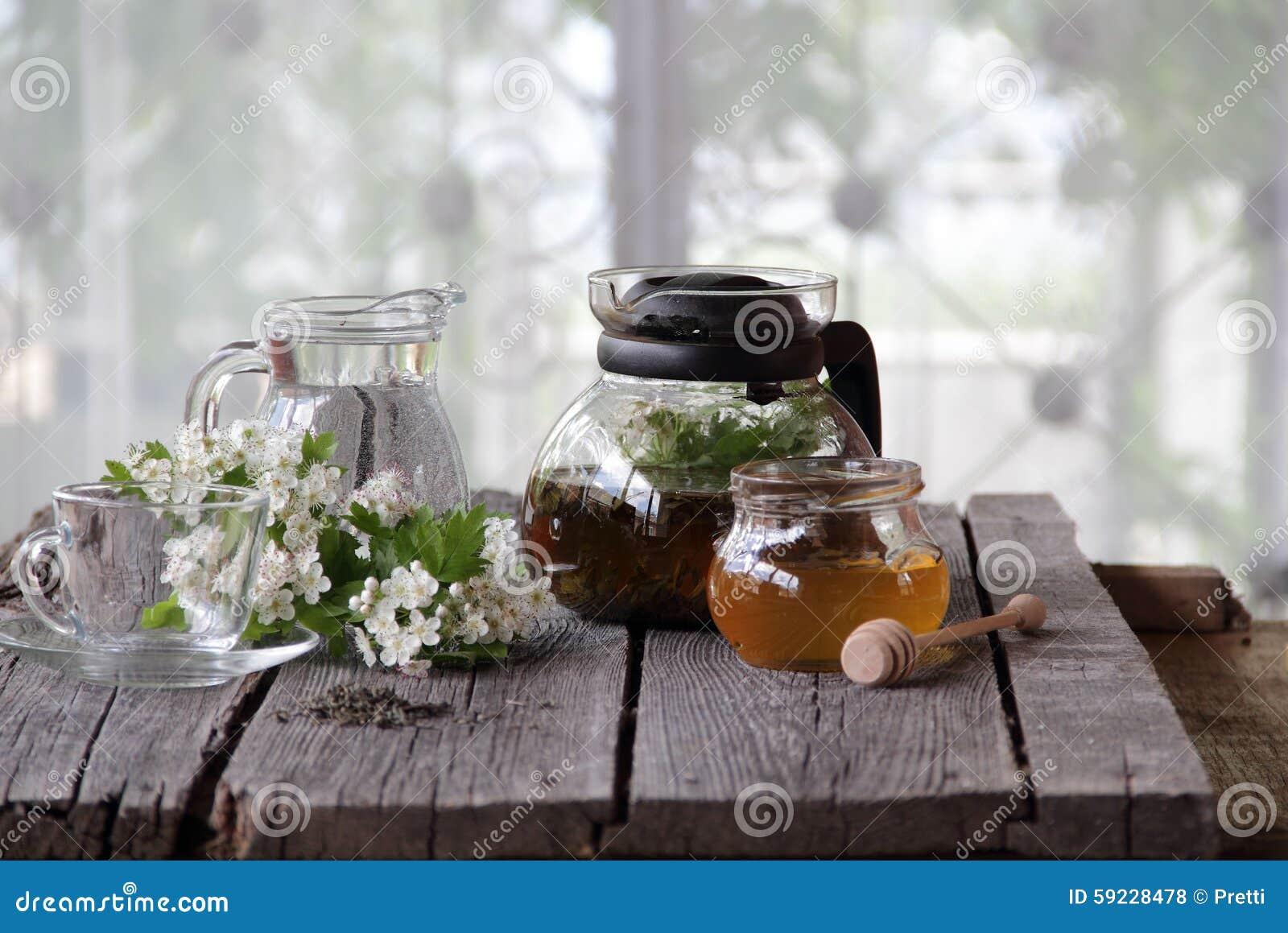 Té verde en una tetera y una miel de cristal y una rama de un blossomi