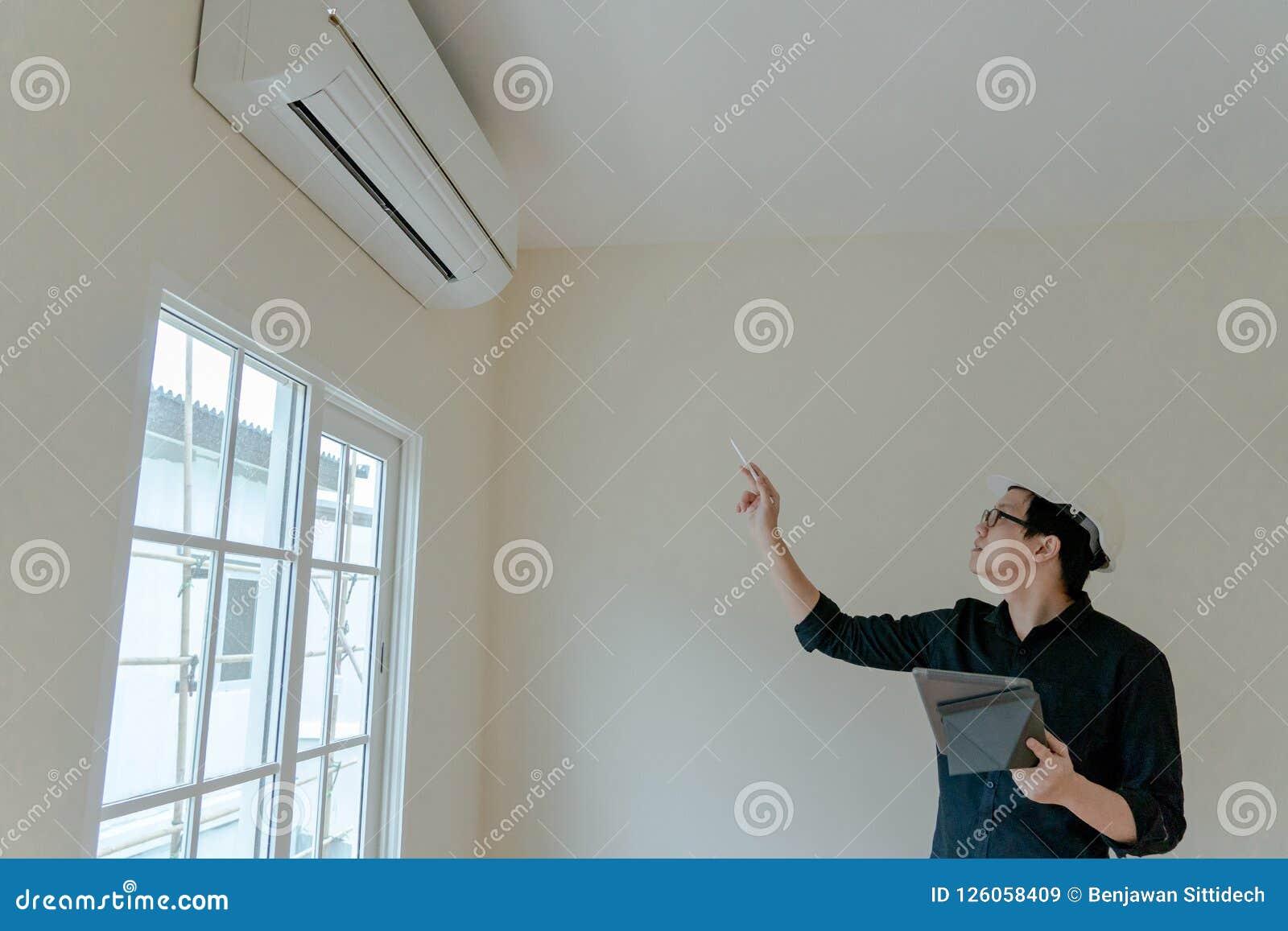 Técnico asiático que verifica o condicionador de ar