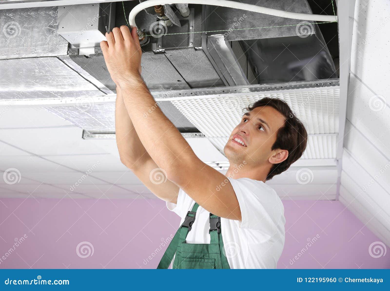 Técnico de sexo masculino joven que repara el acondicionador de aire