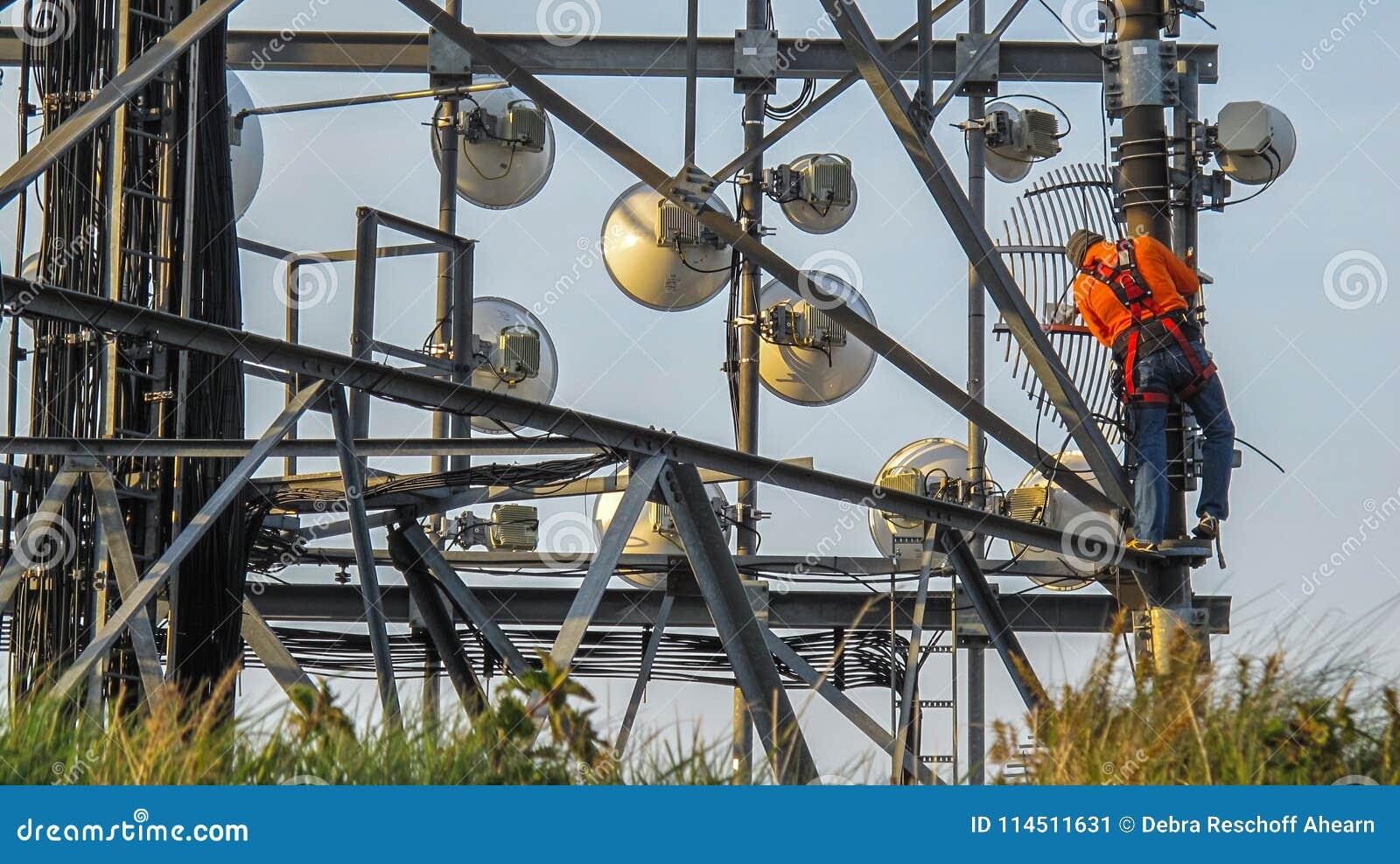 Técnico de trabalho acima de uma torre das telecomunicações