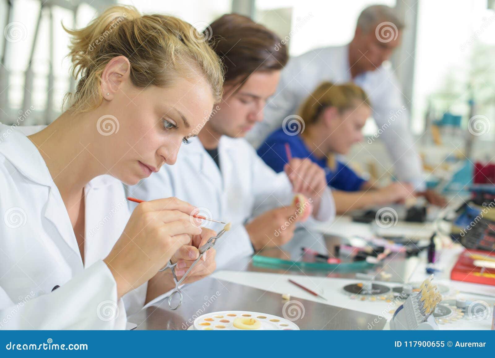 Técnico fêmea que adiciona a cor ao dente falso