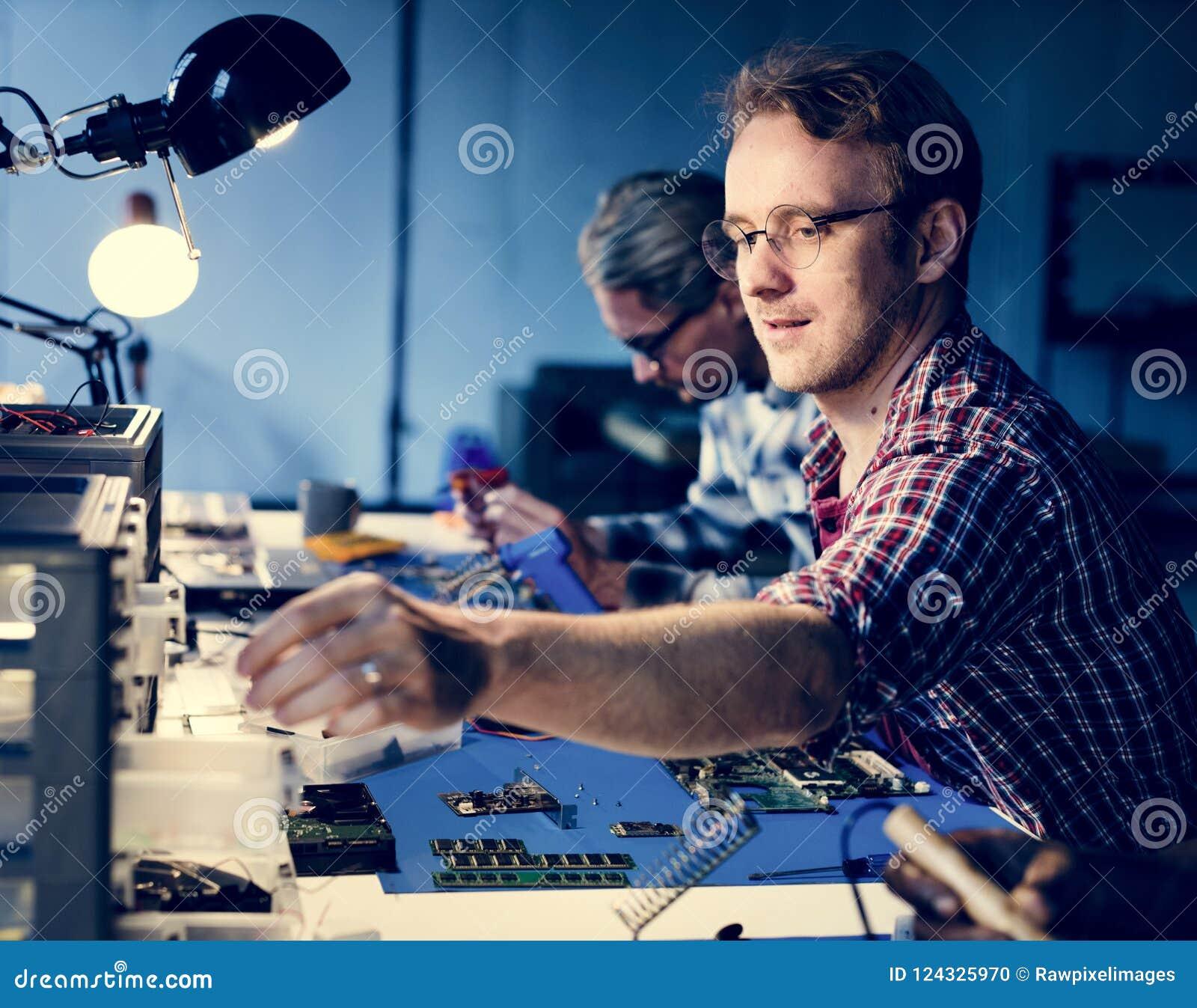 Técnicos bondes que trabalham nas peças da eletrônica