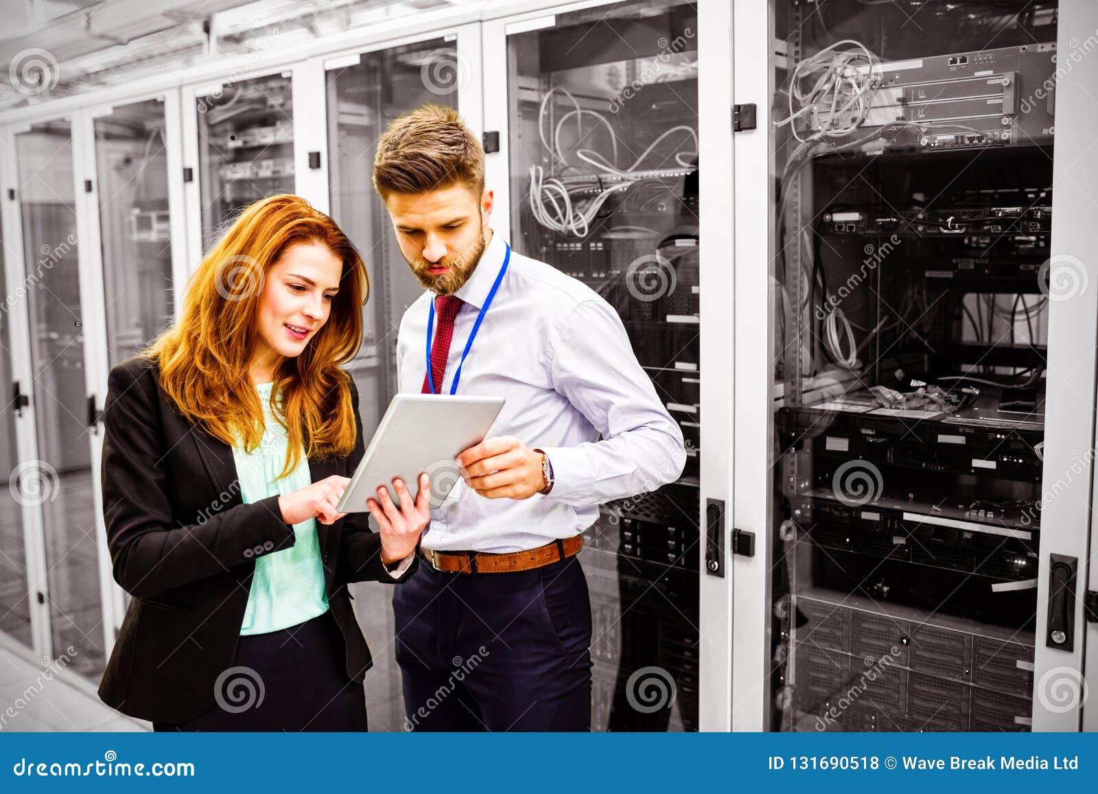 Técnicos que usam a tabuleta digital ao analisar o servidor