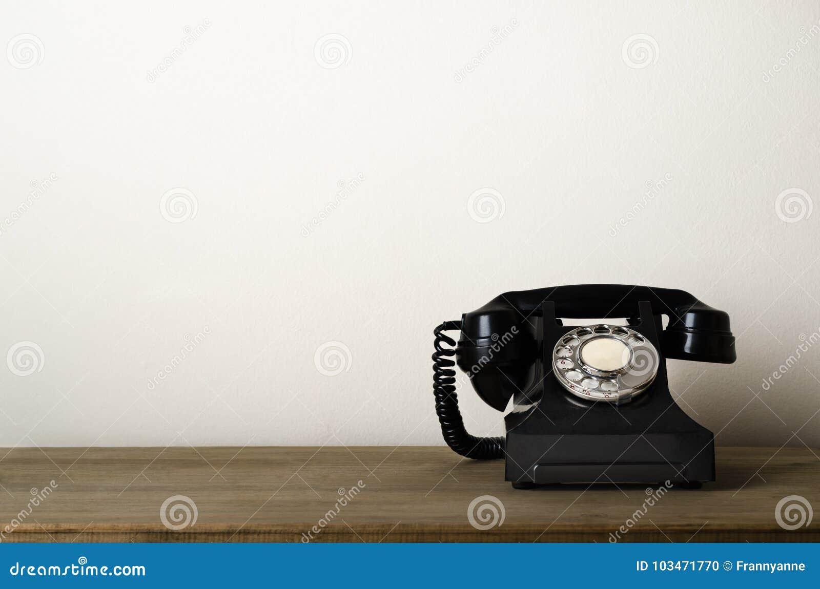 Téléphone antique noir de vintage sur le bureau en bois photo