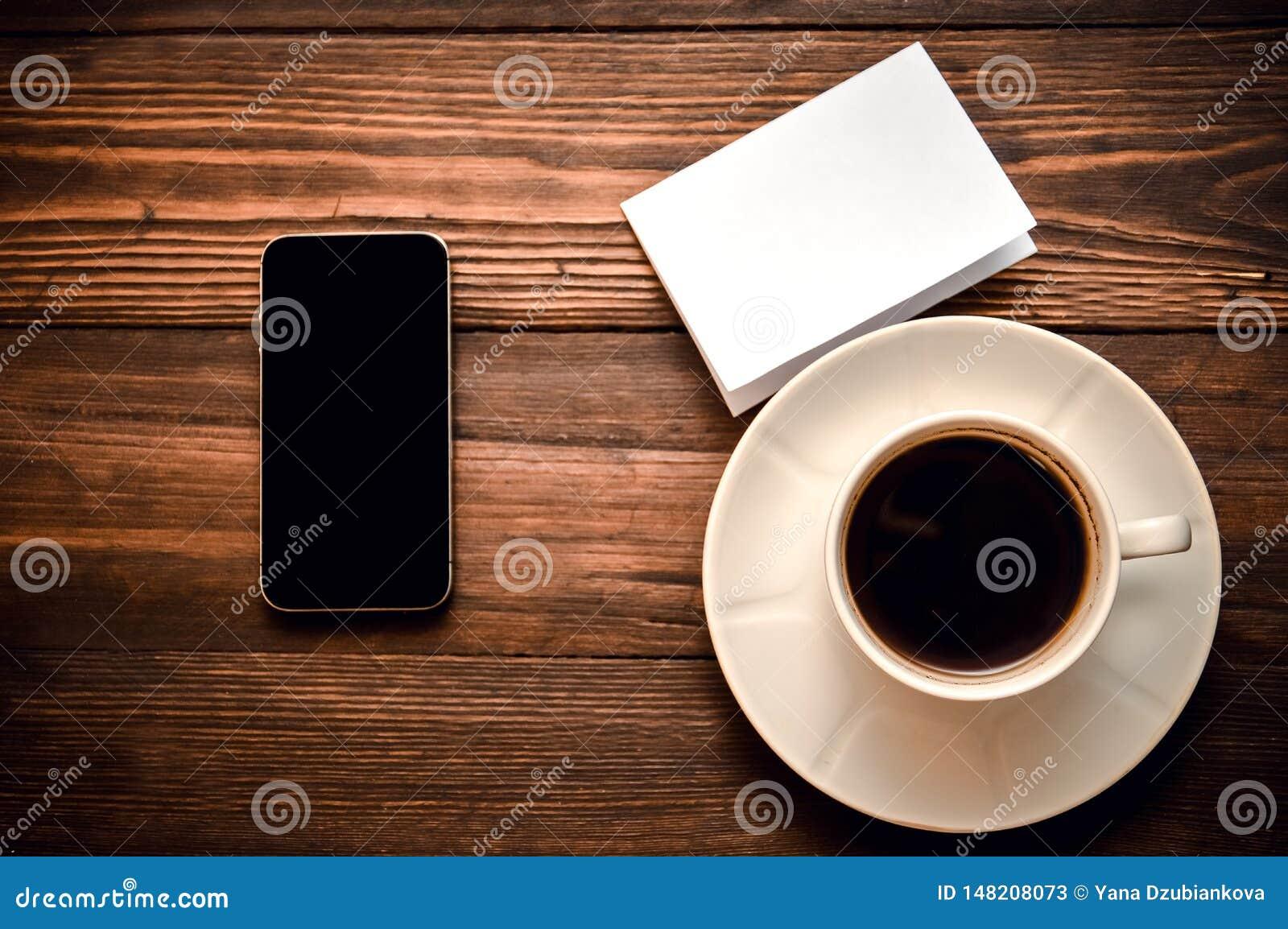 Téléphone avec une tasse de mensonges de café et de livre blanc sur un fond en bois