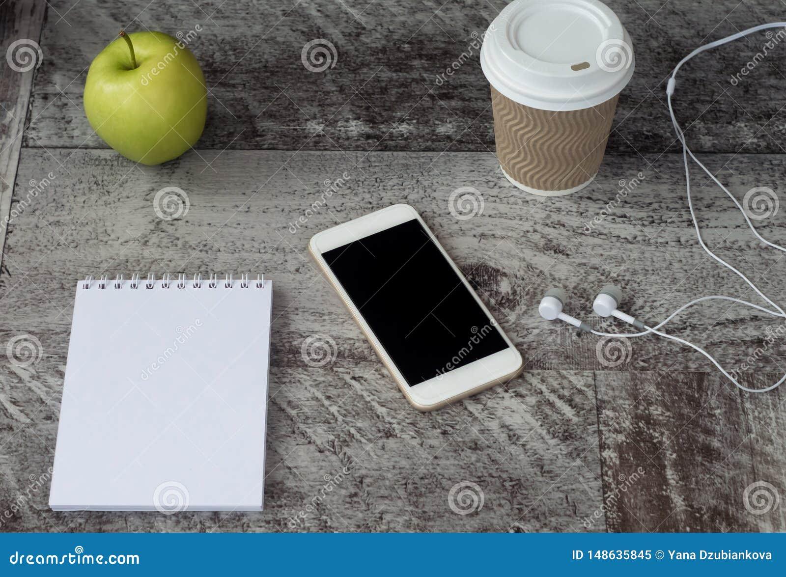 Téléphone blanc avec les écouteurs, le café, le bloc-notes et la pomme verte sur la table Travail ? la maison ind?pendant