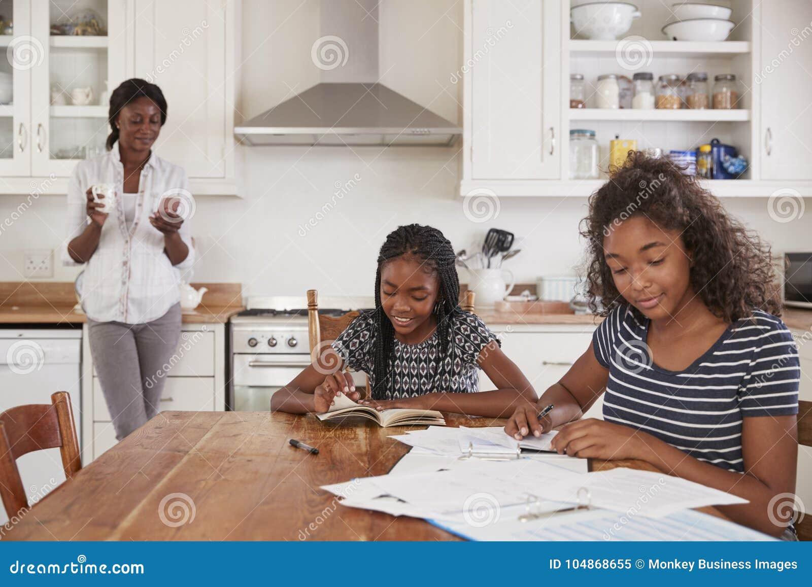 Téléphone d utilisations de mère comme filles Sit At Table Doing Homework