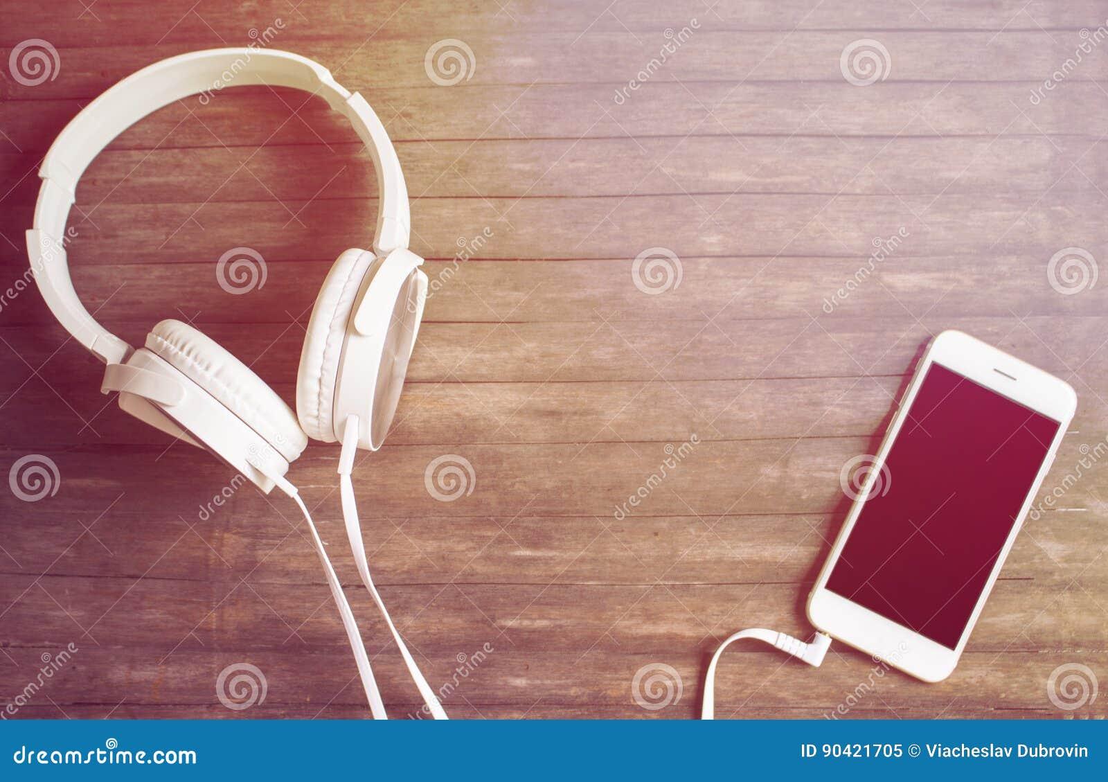 Téléphone et écouteurs blancs sur la table en bois Photo modifiée la tonalité jaune chaude