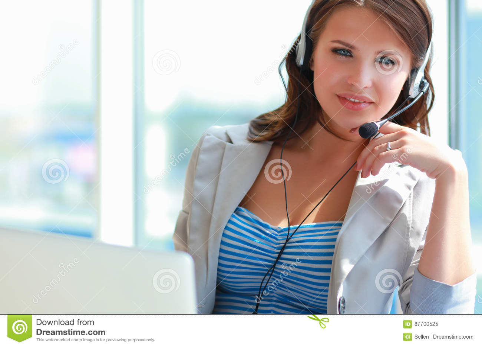 Téléphone parlant de femme d affaires tout en travaillant sur son ordinateur au bureau