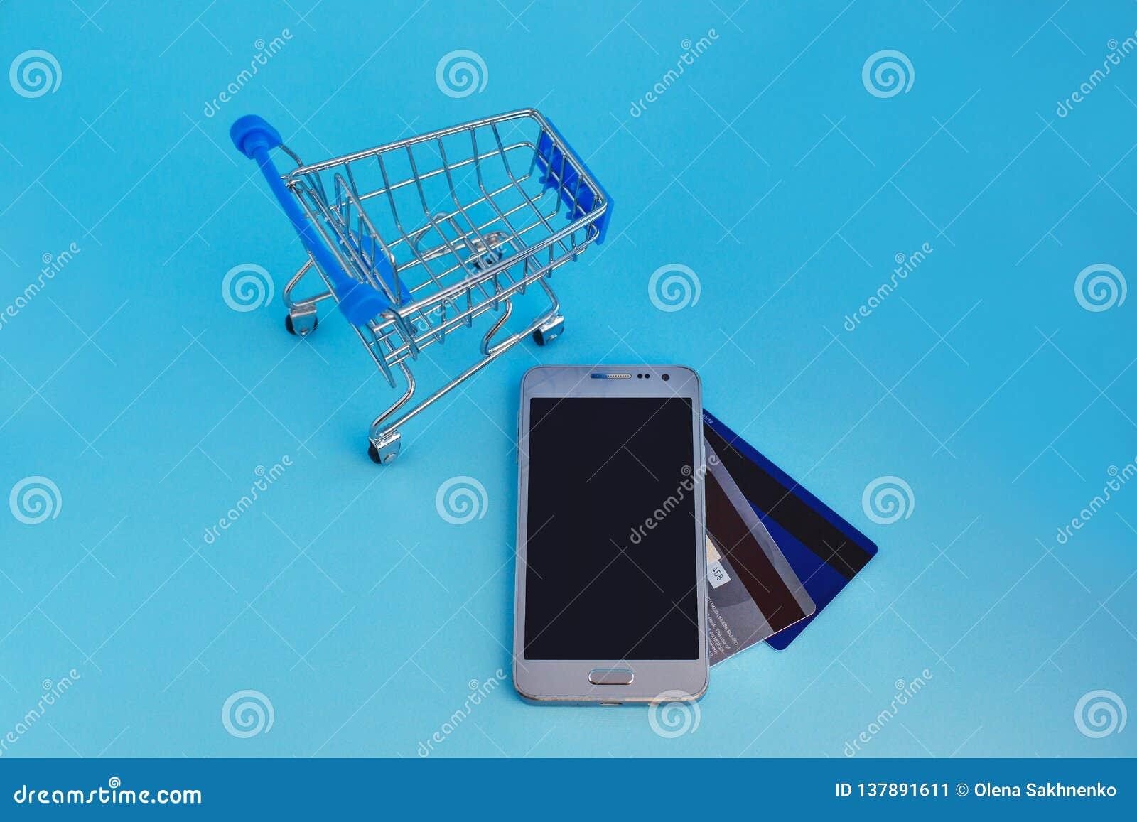 Téléphone portable de caddie et cartes de crédit sur le fond bleu