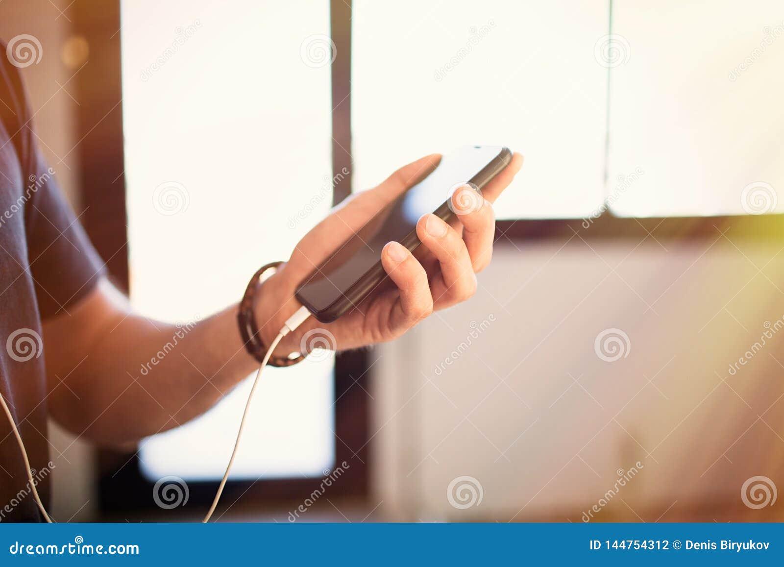 Téléphone portable masculin de participation de mains, vérifiant les réseaux sociaux sur le smartphone à la maison