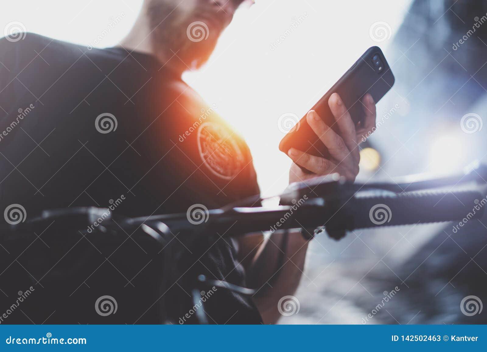 Téléphone portable musculaire tatoué de participation de mâle les mains et en employant l appli de carte pour préparer l itinérai