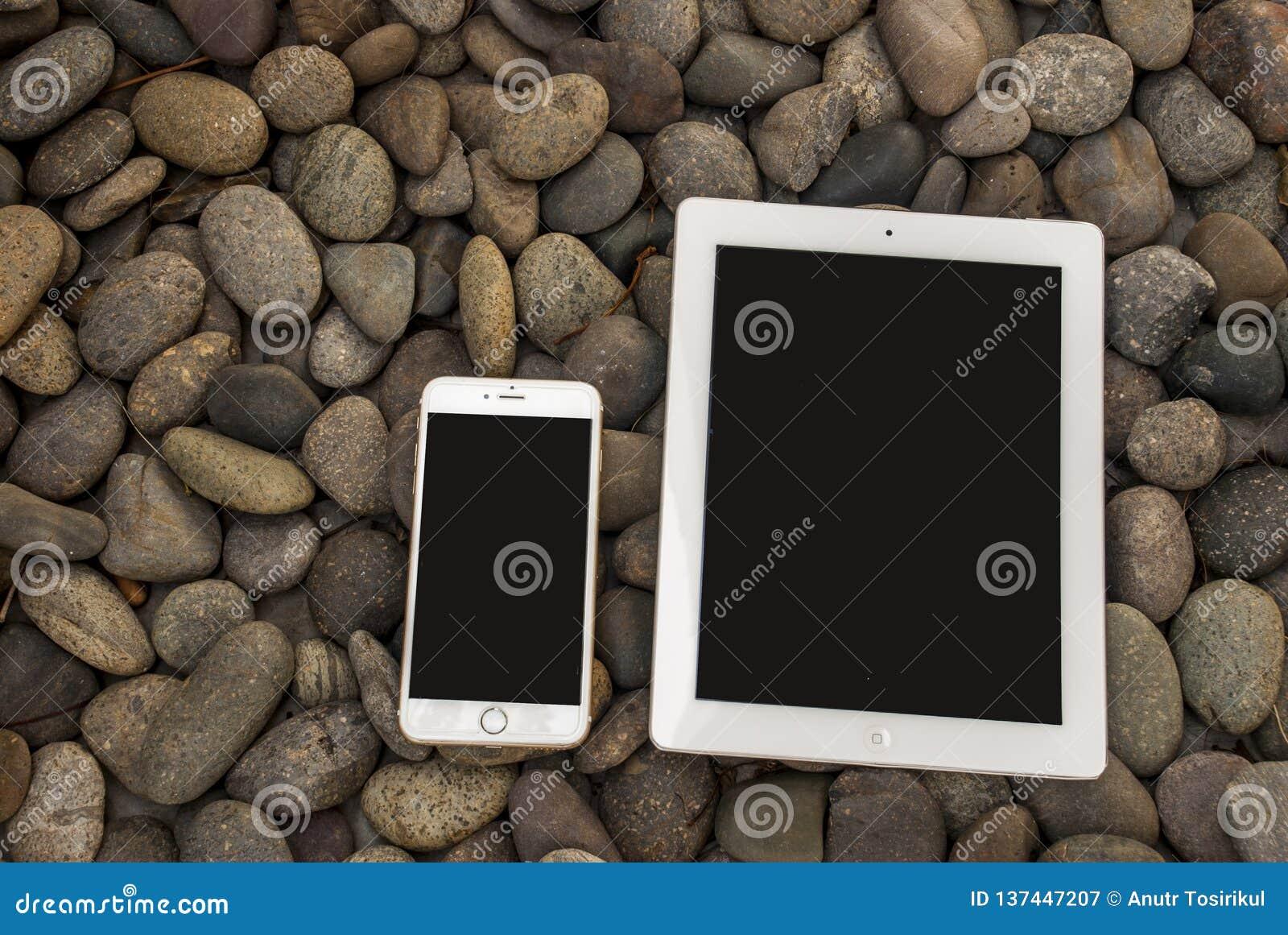 Téléphones portables et Tablette qui sont placés sur une pile des pierres