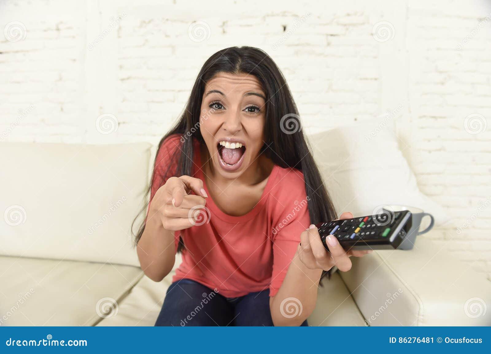 Télévision de observation heureuse riante et de sourire de femme à la maison de divan latin attrayant de sofa