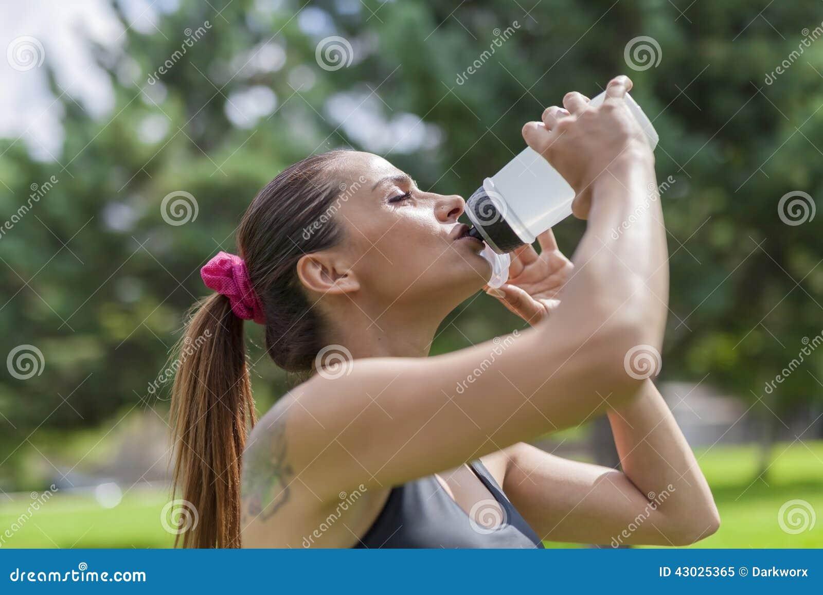 Törstigt dricksvatten för ung kvinna, medan vila