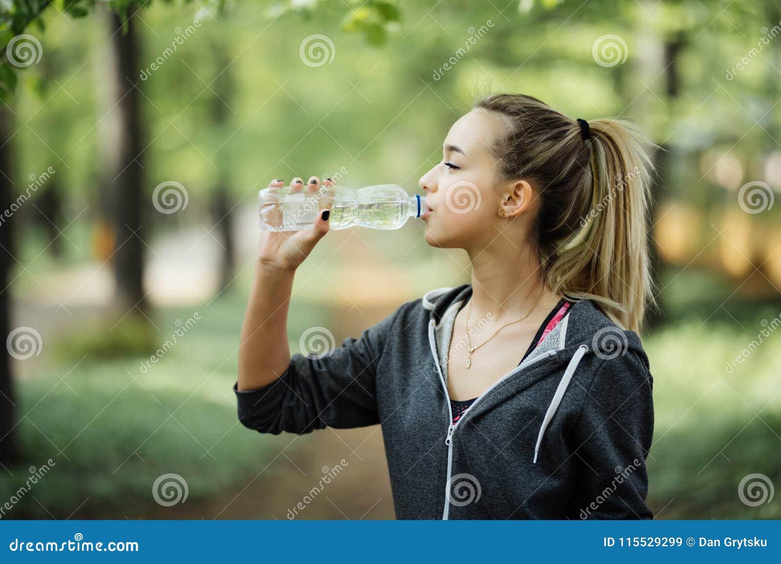 Törstigt kvinnadricksvatten som ska återfås krafter, når det har joggat i stad, parkerar
