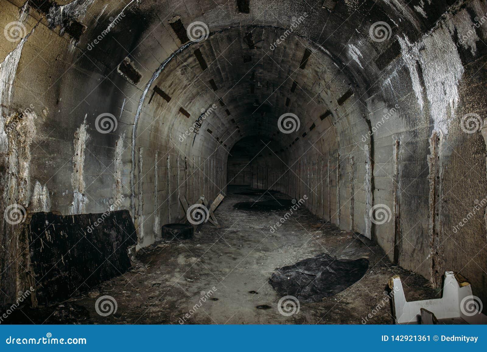 Túnel o pasillo subterráneo largo en arcón o el sótano militar soviética abandonada con la atmósfera espeluznante