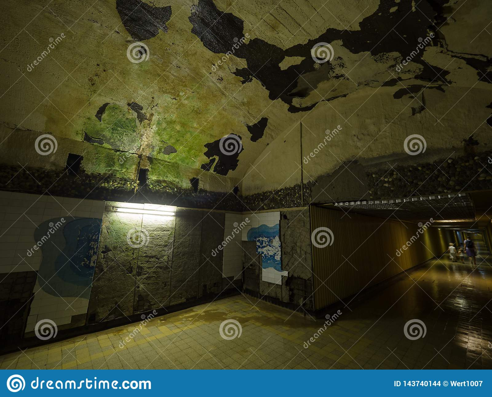 Túnel subterrâneo abandonado velho, paredes com descascamento da pintura e do emplastro