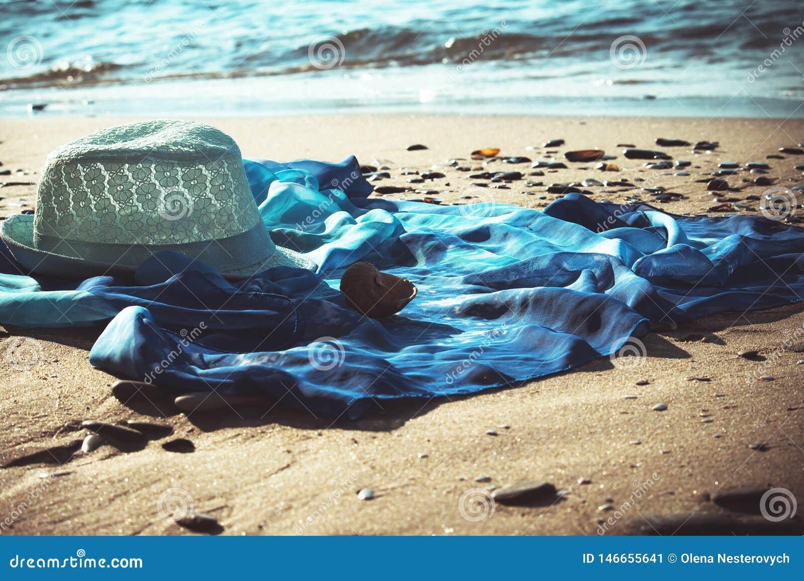 Túnica do chapéu e da praia na praia com o mar no fundo