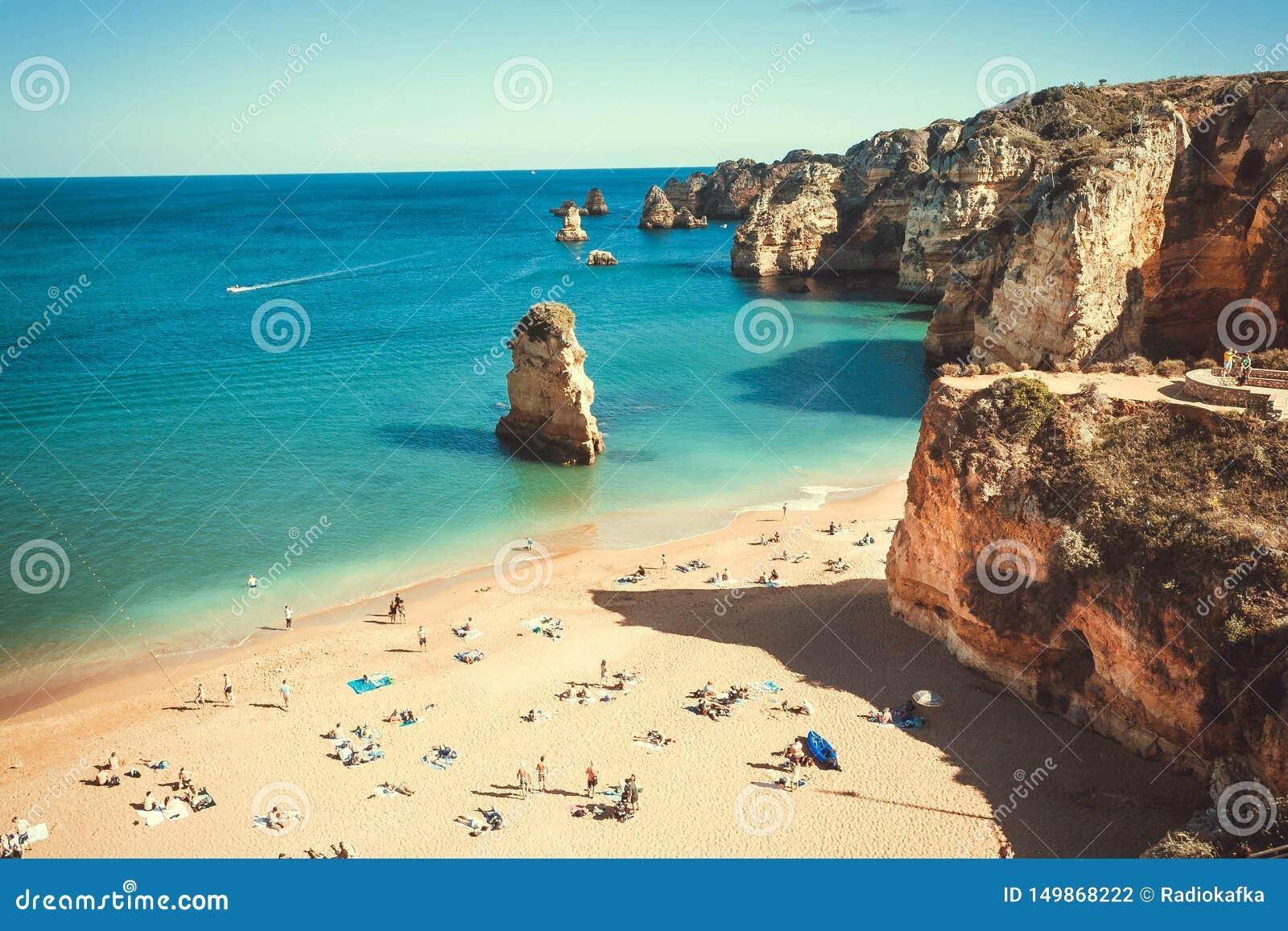 Türkisozean und Küste von Portugal Viele Leute auf sonnigem Strand und ruhigem Wasser am schönen Tag von Lagos