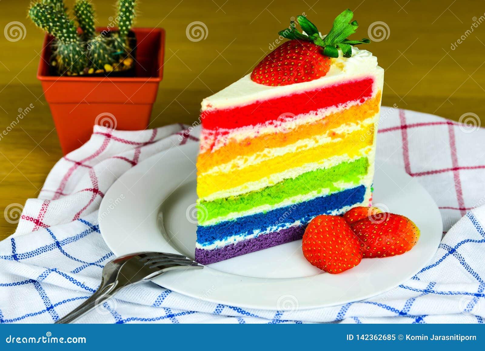 Tęcz truskawki na białym talerzu i tort