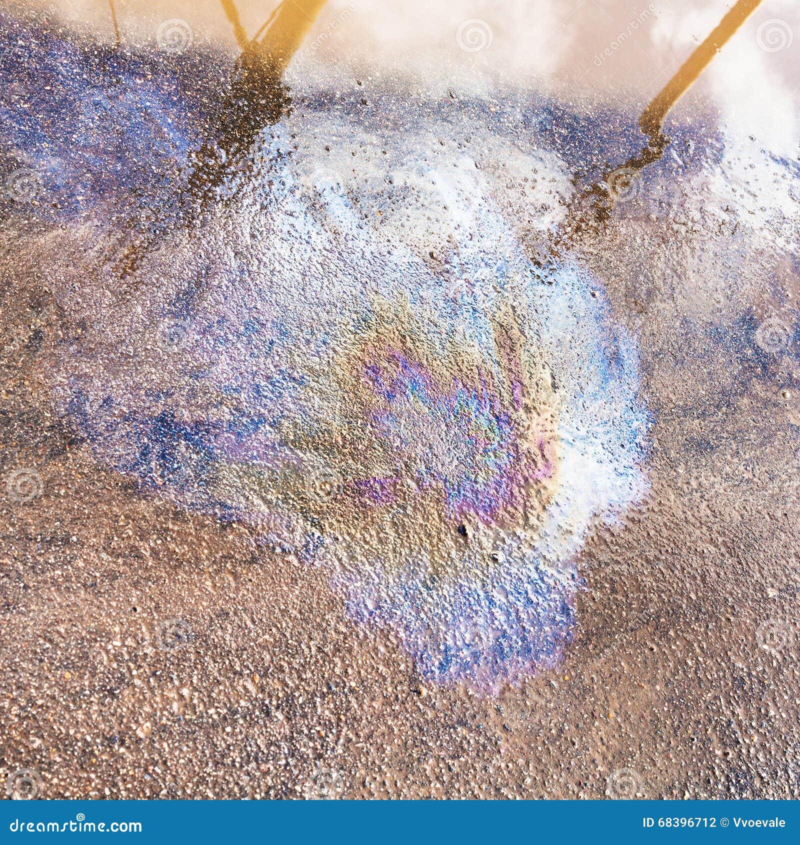 Tęczy plama motorowy olej na mokrym asfaltowym bruku