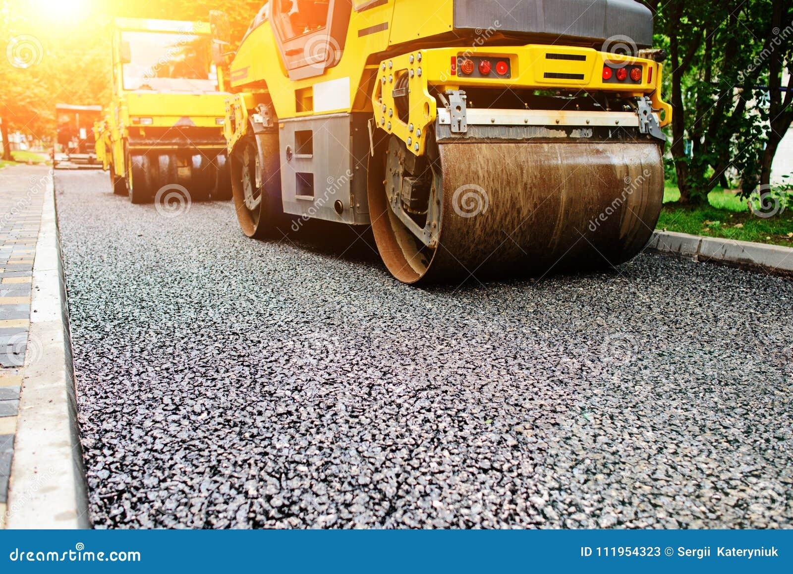 Tło asfaltowy rolownik który broguje gorącego asfalt i naciska Drogi remontowa maszyna