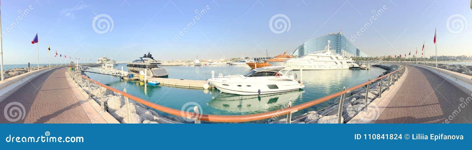 Tło panoramy widok Perska zatoka, marina i chodzący teren Jumeirah hotel, jachty i woda park,
