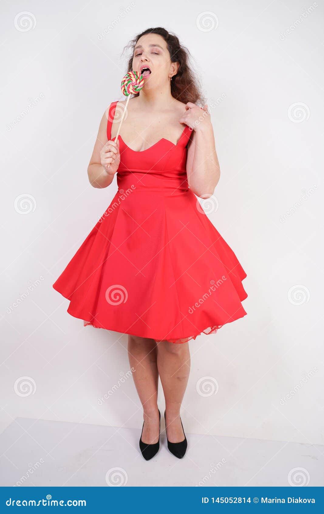Tłuściuchna kobieta w czerwonej pinup sukni pyzata modna dziewczyny pozycja na białym tle w studiu