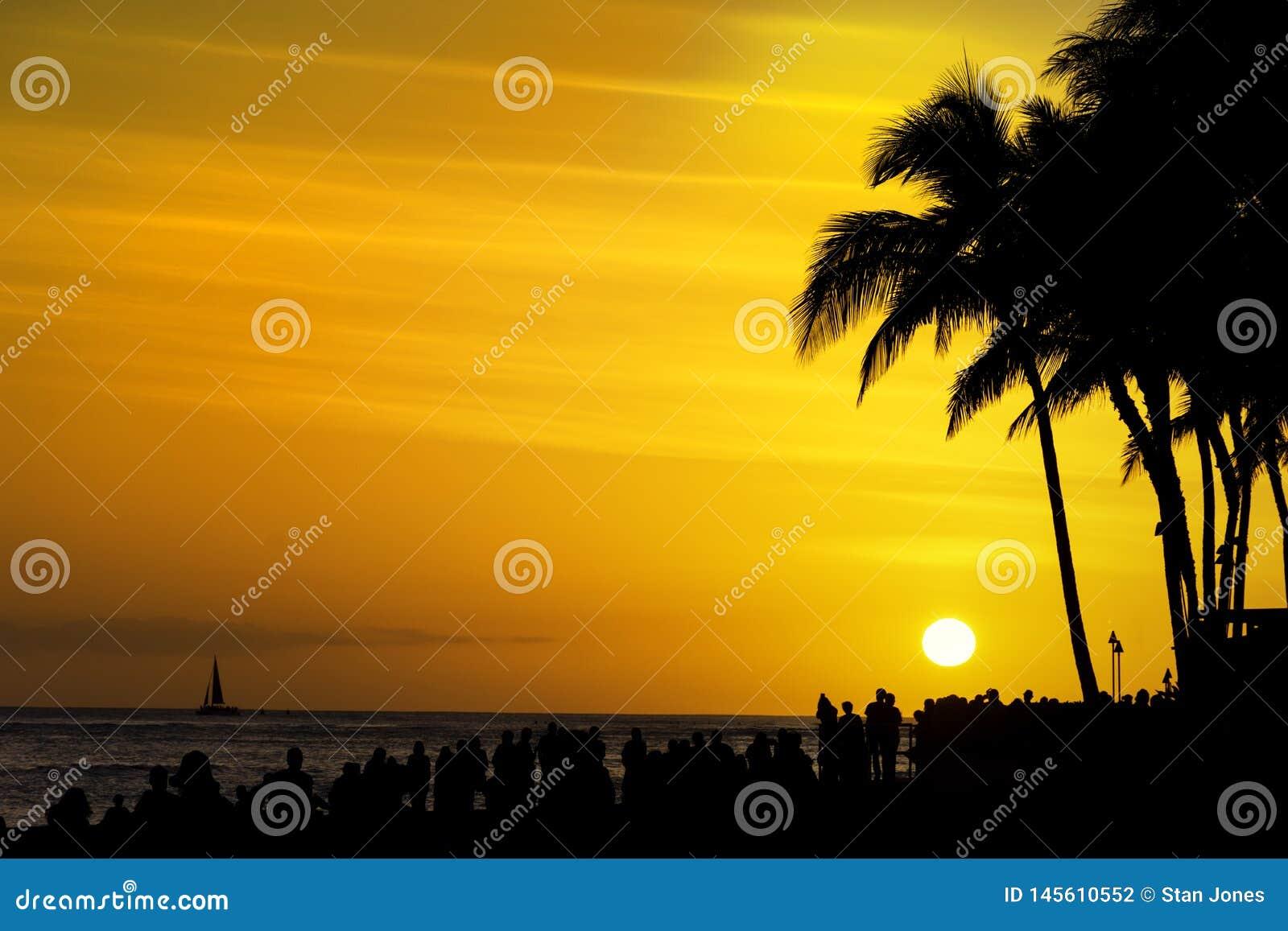 Tłumy turyści zbierają oglądać zmierzch na Waikiki plaży Honolulu Oahu Hawaje usa