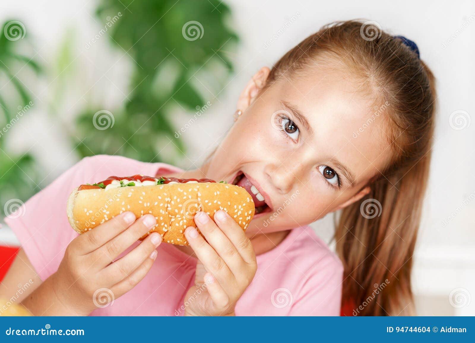 T恤杉的年轻逗人喜爱的欧洲女孩吃象热狗和芯片的不健康的食物