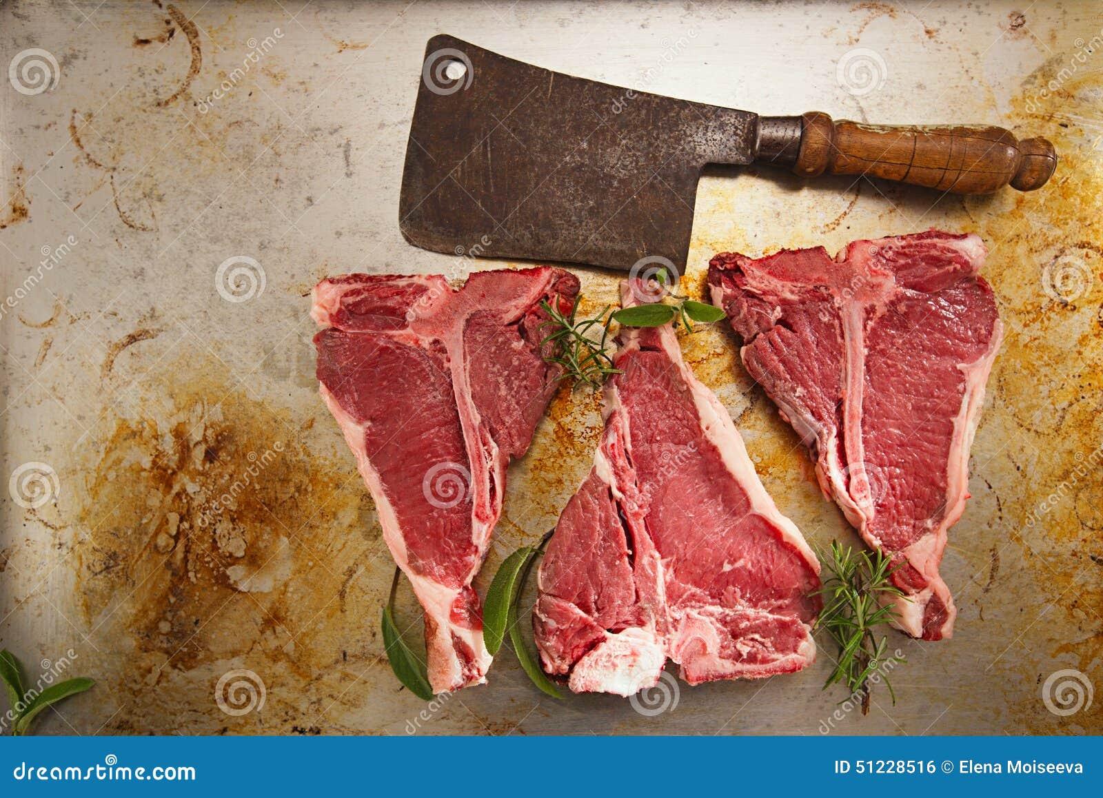 T-косточка стейка говядины с винтажным ножом дровосека мясника