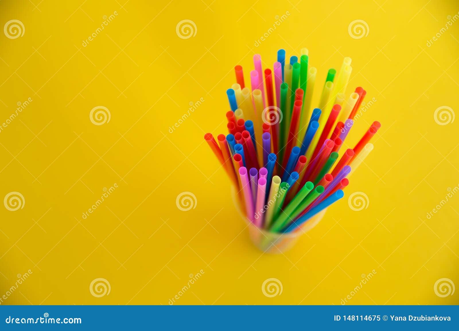 T?bulos pl?sticos multicolores para un c?ctel en un vidrio en un fondo blanco Pol?meros en vida cotidiana