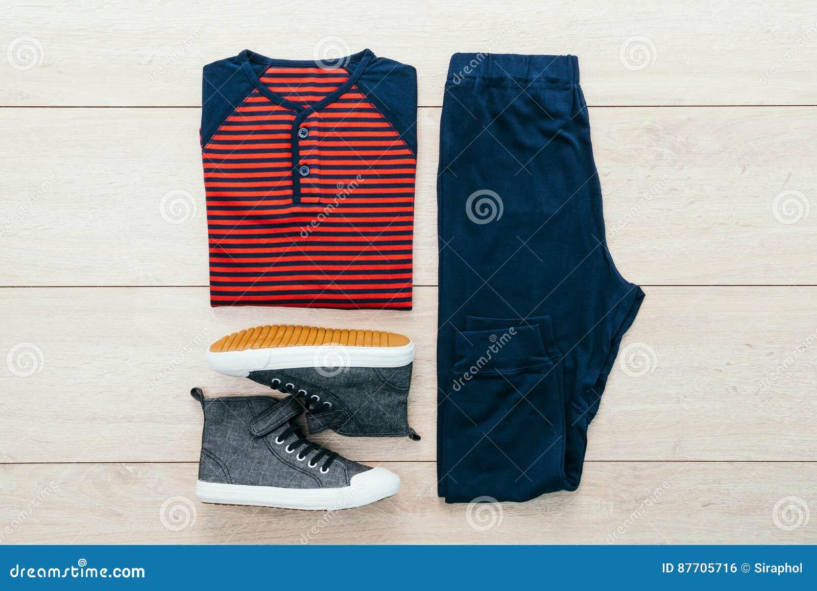 T-shirt avec le pantalon et les chaussures sur le fond en bois