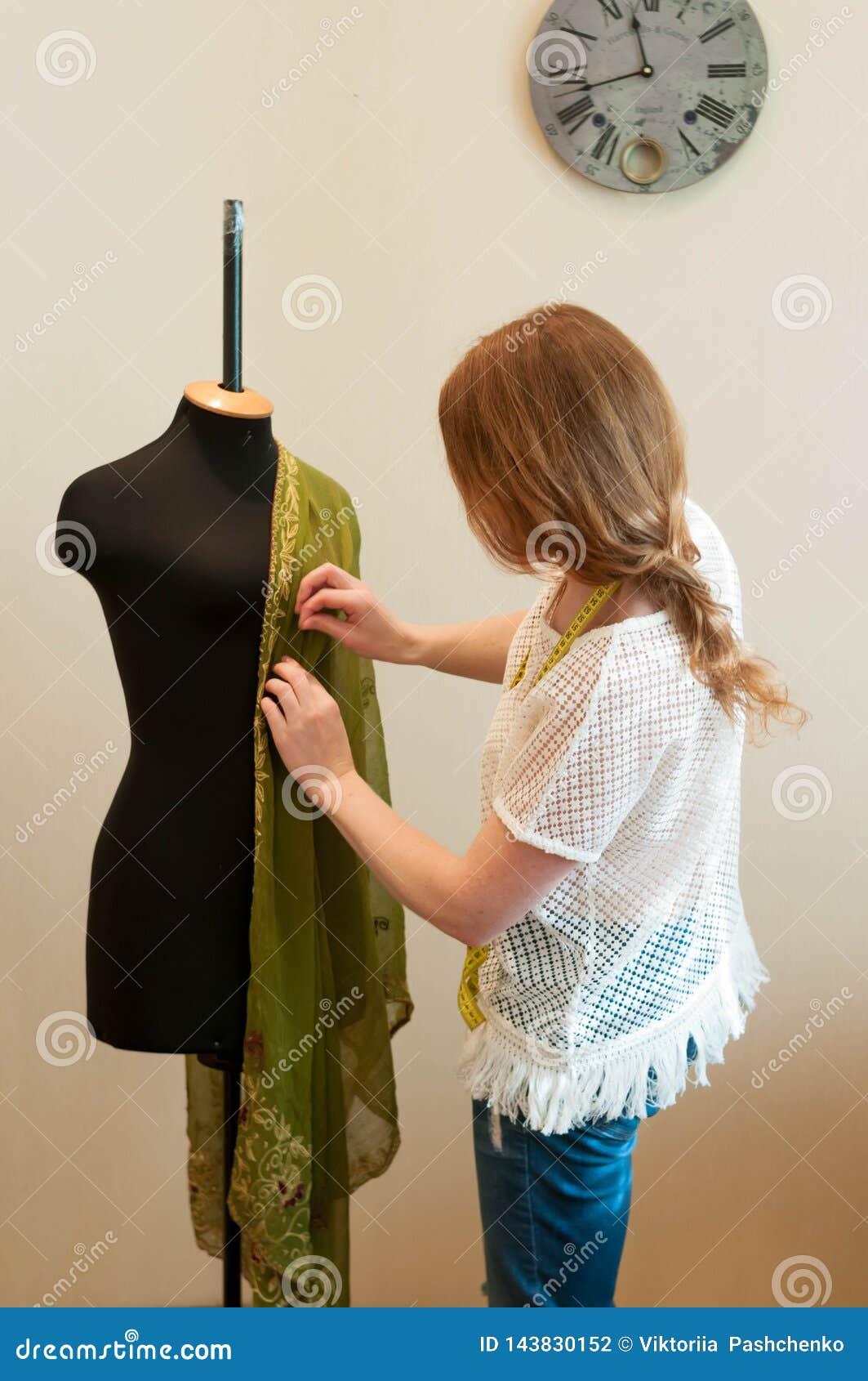 T-shirt et jeans tenant et modelant des vêtements avec le tissu vert sur le mannequin noir